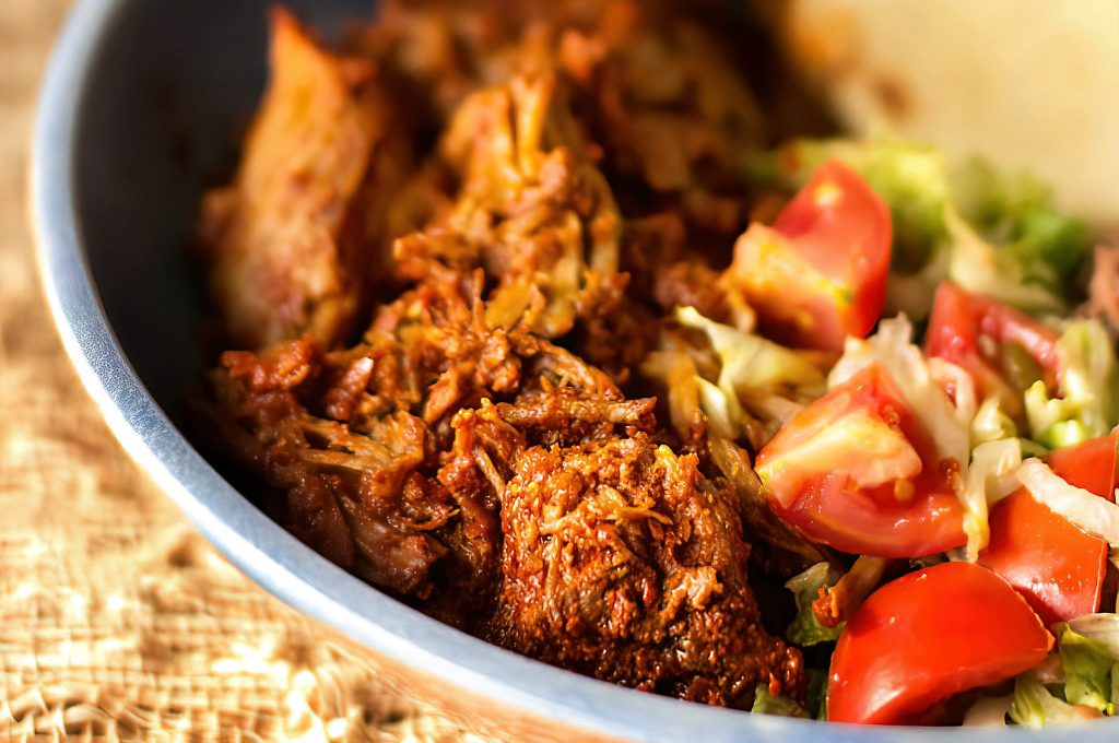 MJ's Kitchen Image of Carne Adovada with lettuce shreds and cherry tomatoes.